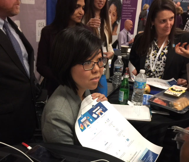 Photo of asian woman in a suit with a flyer and people standing around her