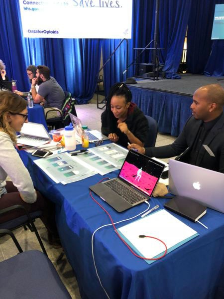 Two women and a man at a table, coders at the HHS Opioid Code-a-Thon