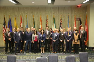 Group of people standing in front of world flags: the Global Digital Health Partnership