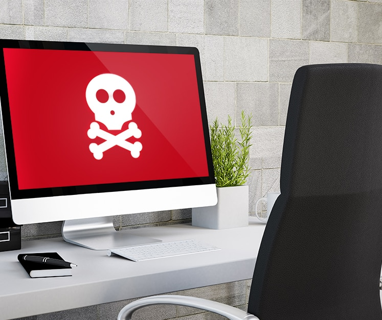 A desktop computer with an image of skull and crossbones on the screen.
