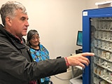 "Deputy Secretary Eric Hargan looks at a medicine ""vending machine"" - thumbnail image"