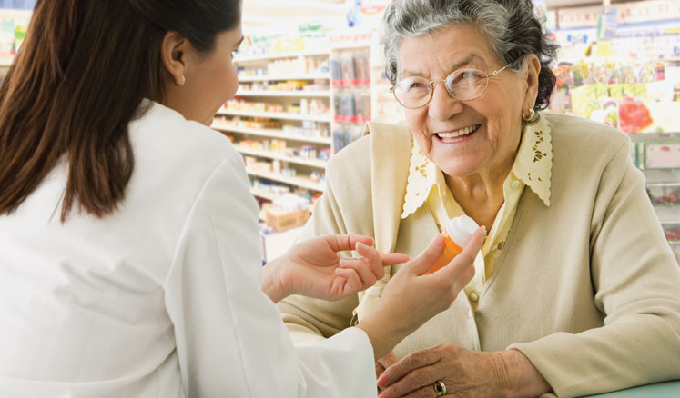 An elderly woman gets medication from a pharmacist