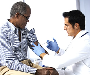 Doctor giving shot to a middle-aged man