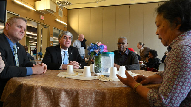 Assistant Secretary Lance Robertson and Deputy Secretary Eric Hargan at a table, speaking with a Walter Reed Community and Senior Center client