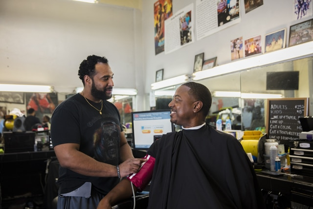Eric Muhammad (left), owner of A New You Barbershop in Inglewood, California, prepares to measure the blood pressure of long-time customer Marc Sims. Photo credit: Smidt Heart Institute at Cedars-Sinai Medical Center.