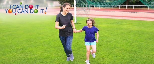 Girl and young woman running on a grassy sports field