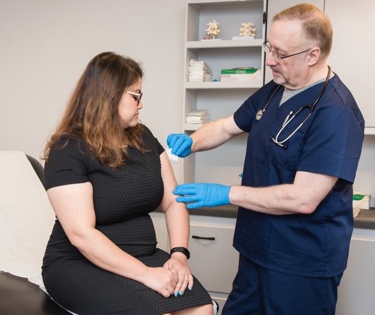 Doctor prepping woman's arm for vaccination.
