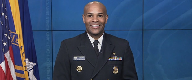 U.S. Surgeon General, VADM Jerome Adams in uniform centered in front of blue background.