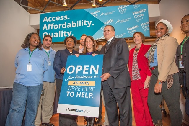 "Secretary Burwell poses with the ""Here to Help"" sign for 2016 Open Enrollment during a trip to Atlanta, Georgia."