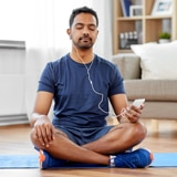 man on yoga mat with headphones in meditating