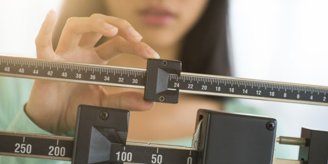 Woman adjusts weight scale