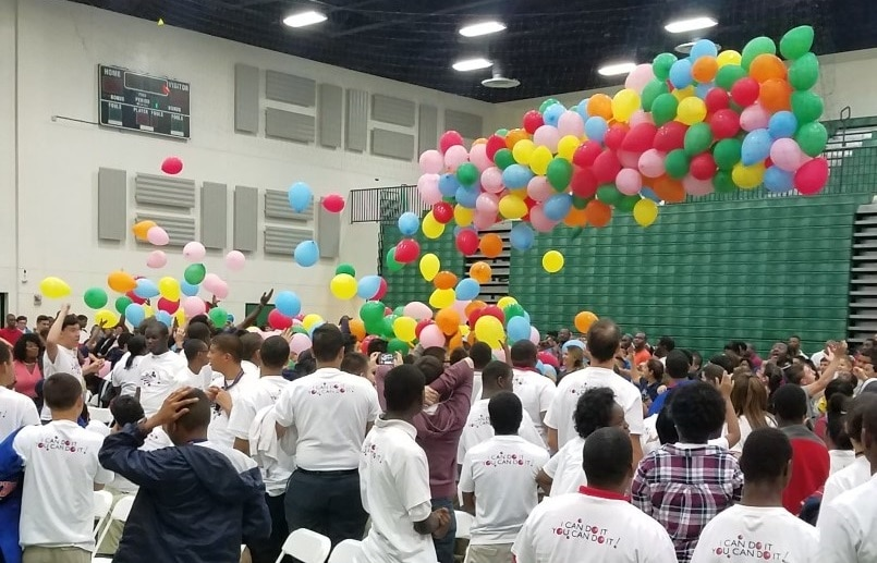 Photo of students celebrating as balloons fall in auditorium