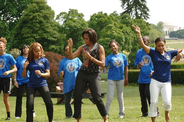 First Lady Michelle Obama, and PCFSN Co-Chiar and Olympian Dominque Dawes lead a dance during a PALA+ event.