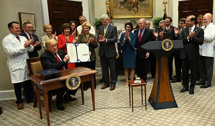 President Trump signs legislation that bans pharmacy gag clauses.