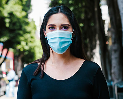 Portrait of a young adult woman with face mask standing outside.