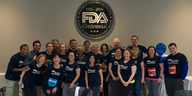 Mike Sauers (back/right) poses with other staff members of FDA's Office of Prescription Drug Promotion's (OPDP). Photo Credit: FDA.