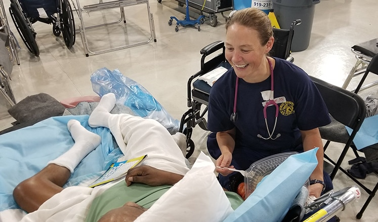 LT. Carin Molchan, RN, a nurse with the U.S. Public Health Service cares for a patient at a medical shelter in Clayton, NC.