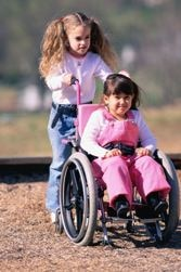 A girl pushes another girl in a wheelchair