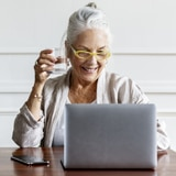 senior woman using laptop and drinking a glass of water