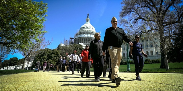 HHS staff walk by the U.S. Capitol.