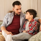 father speaking with young son on couch at home