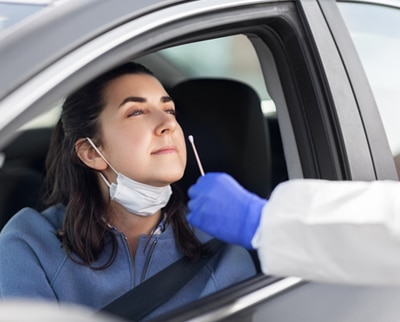 Healthcare worker in protective gear with swab taking a coronavirus test for young woman in her car