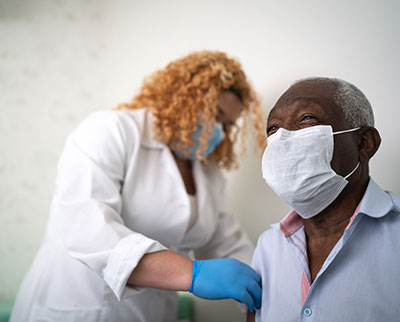 An older male patient wearing a masks sits while a female health care provider wearing a mask and gloves administers a vaccine in his arm.