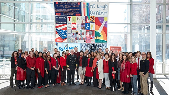 Adm. Brett Giroir stands in front of a portion of the AIDS Memorial Quilt display on the Food and Drug Administration's headquarters with a large group of FDA employees.