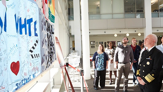Adm. Brett Giroir and a group of employees from the Food and Drug Administration look up at the AIDS Memorial Quilt display.