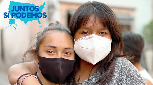Two young people wearing masks embrace and look at the camera. There is an emblem reading 'Juntos Si Podemos' in the upper left corner.